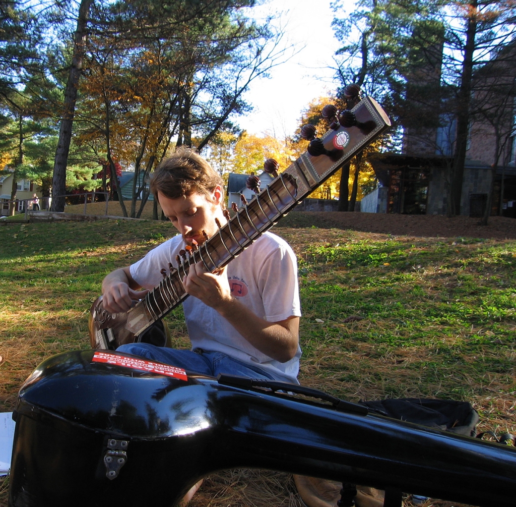 Woody Leslie playing sitar outdoors