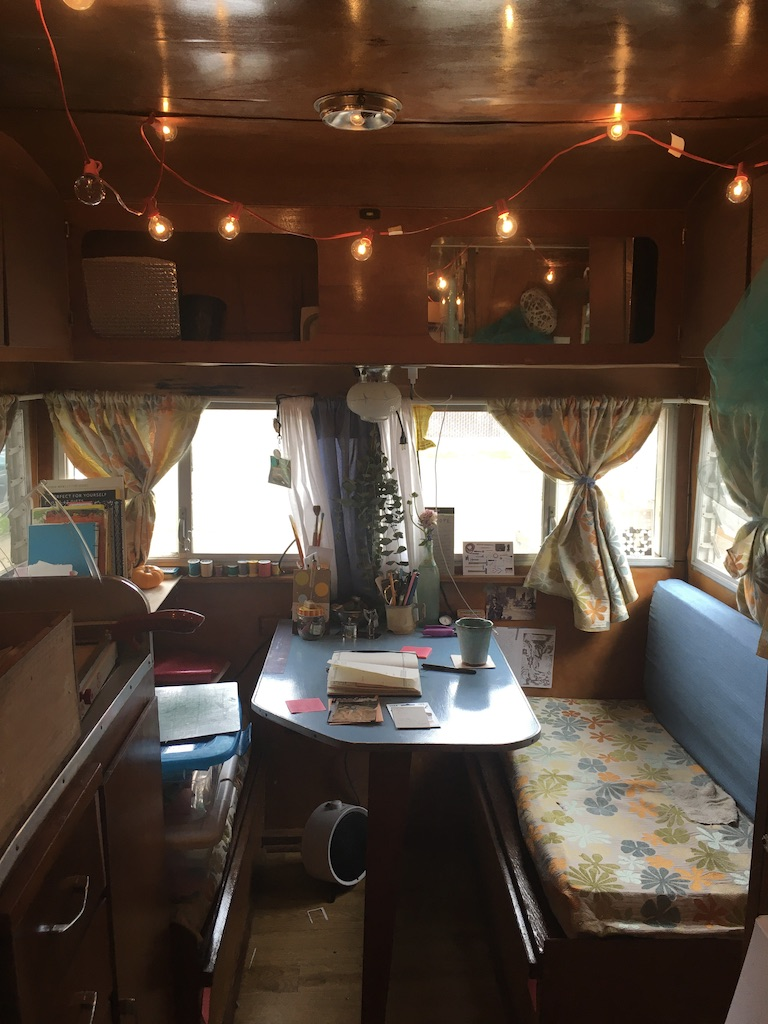 Vintage camper-turned-art studio with paper cutter, collage supplies, journal and coffee mug.