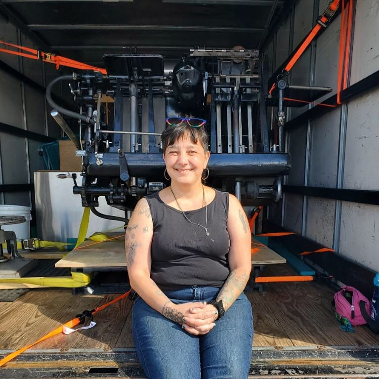 Hope Amico sits smiling in front of a Heidelberg Windmill letterpress in a moving truck.