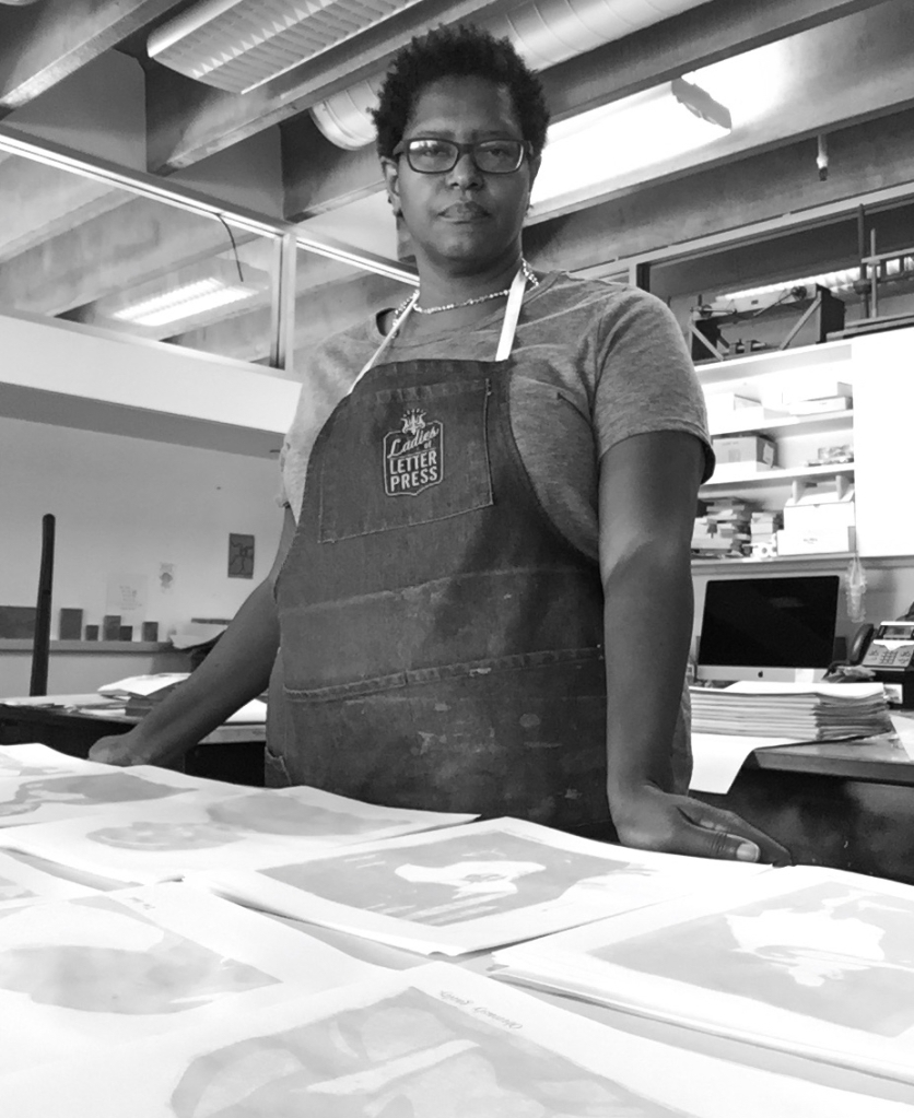 "Black and white portrait of Tia Blassingame examining prints in the studio, wearing a ""Ladies of Letterpress"" apron."