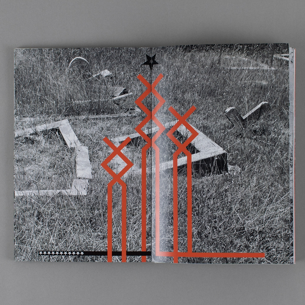 """This Land is My Land, inside opening from early in the book. A black and white photo of a neglected cemetery spans the full spread. Red, abstract symbols based on the """"othala rune"""" are centered in the composition, with black and white stars at the top and bottom left"""