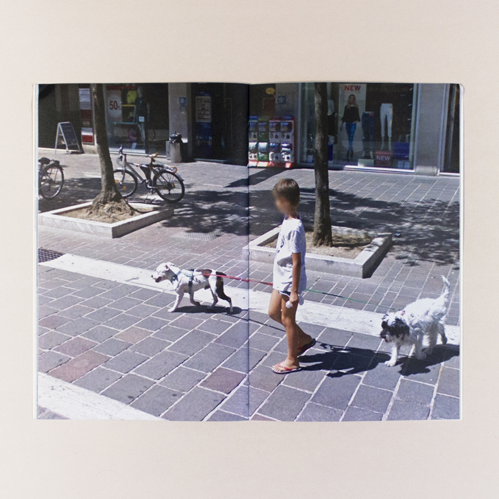 Attenti al Cane, Spread 13. Street View image of a child walking two leashed dogs and carrying a plastic bag. The child's face is blurred.