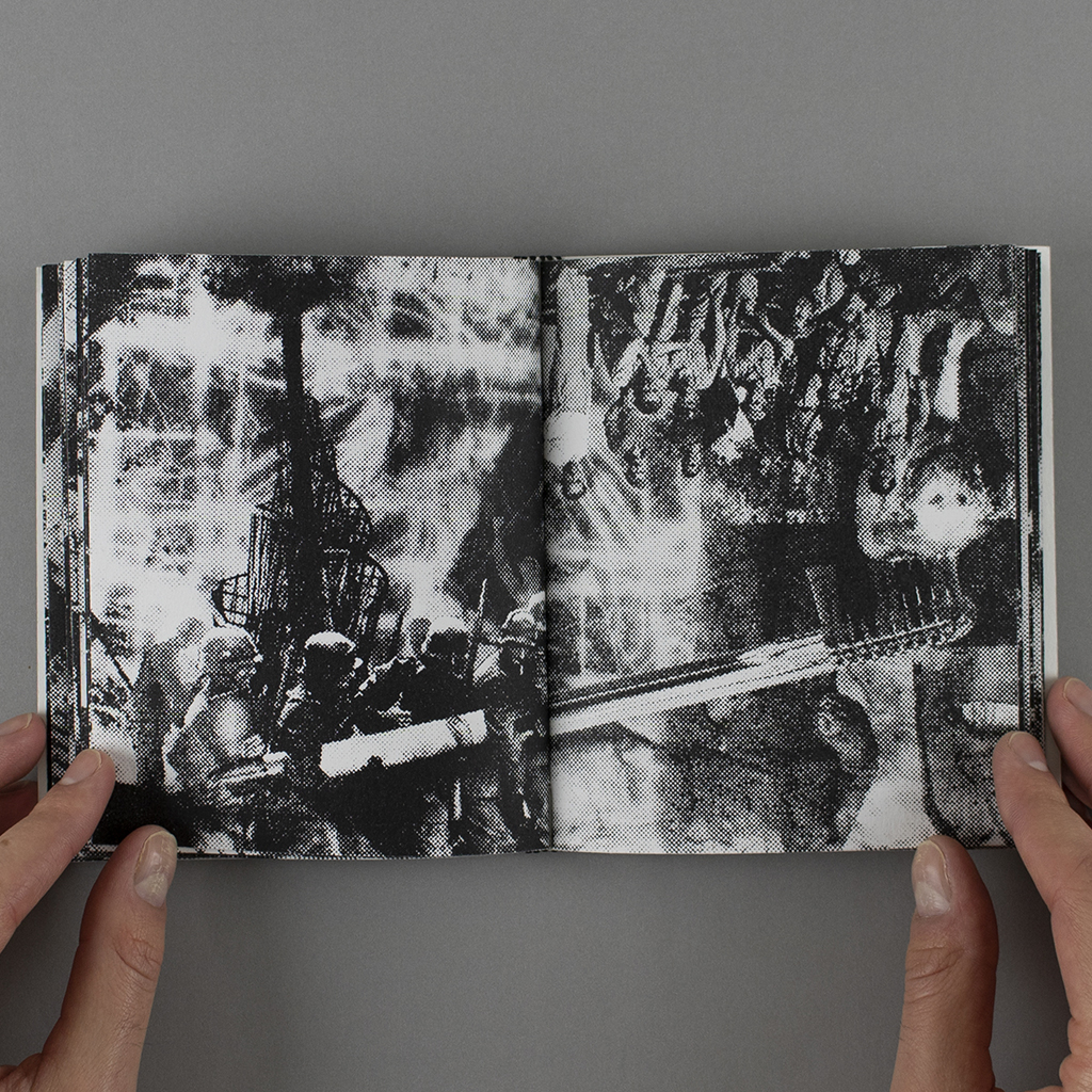 Fragmented Memory, center spread. With Tatlin's Monument to the Third International emerging from a fiery background, a group of soldiers wield an object, which – upon crossing the spread's gutter – becomes a massive toothbrush scratching the back of a dog.