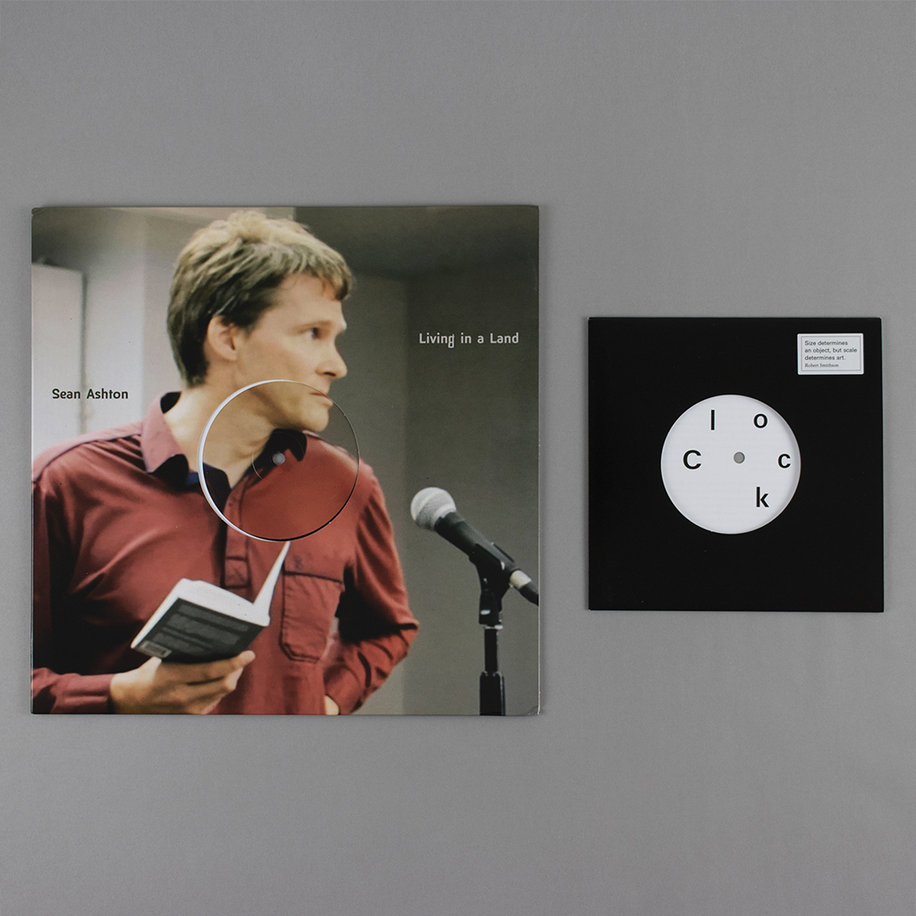 """On the left, a 12-inch vinyl LP of Sean Ashton """"Living in a land"""" which features a photo of the poet reading in front of a microphone. On the right, Craig Dworkin's """"Clock"""" which looks like a 45 rpm in a square slipcase with a circle die cut from the middle."""
